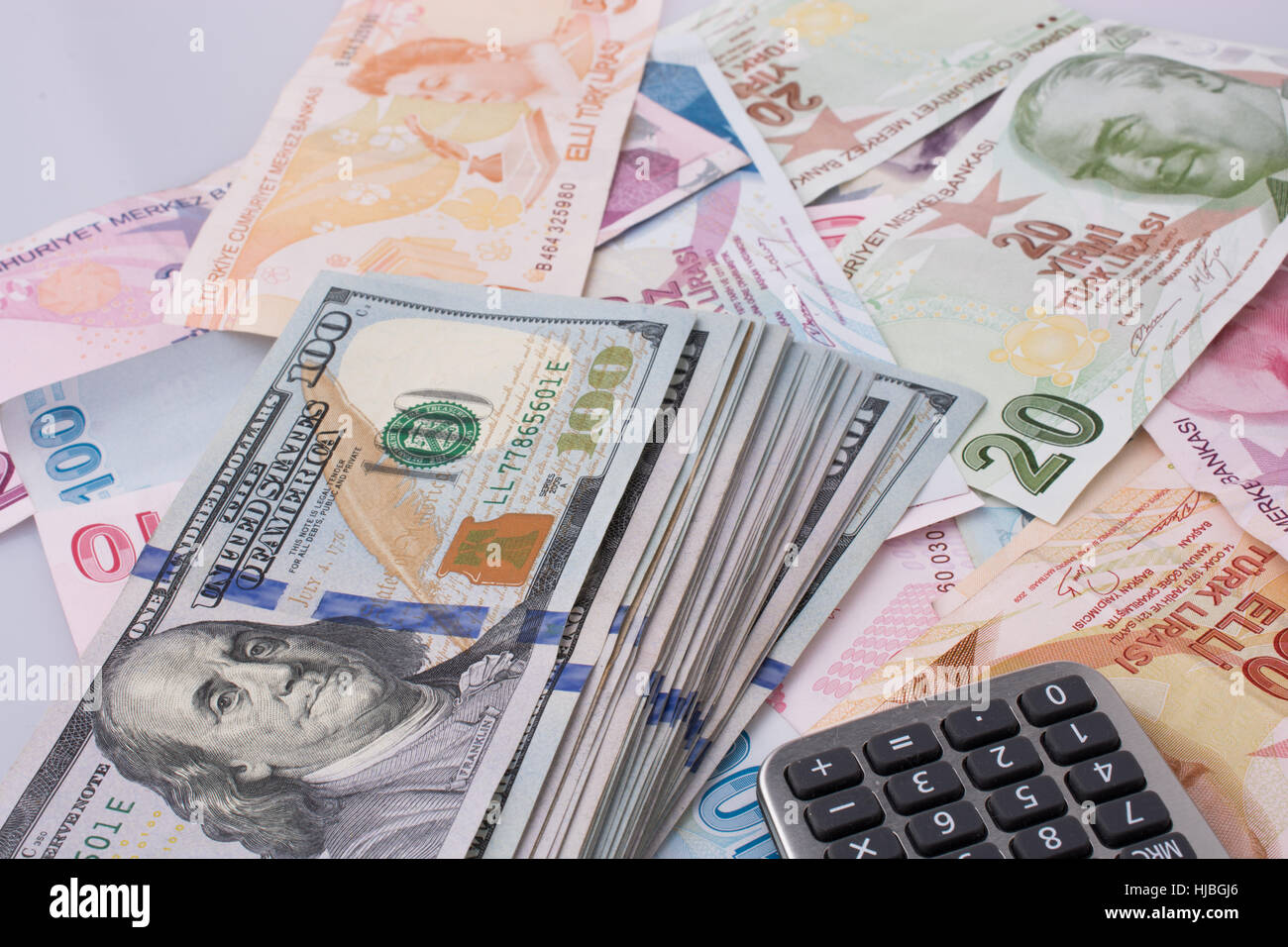 Calculator, American dollar banknotes and Turksh Lira banknotes side by side on white background Stock Photo