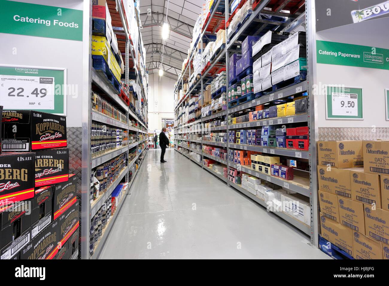 Man standing in aisle of the dry goods section of a wholesaler. - Stock Image
