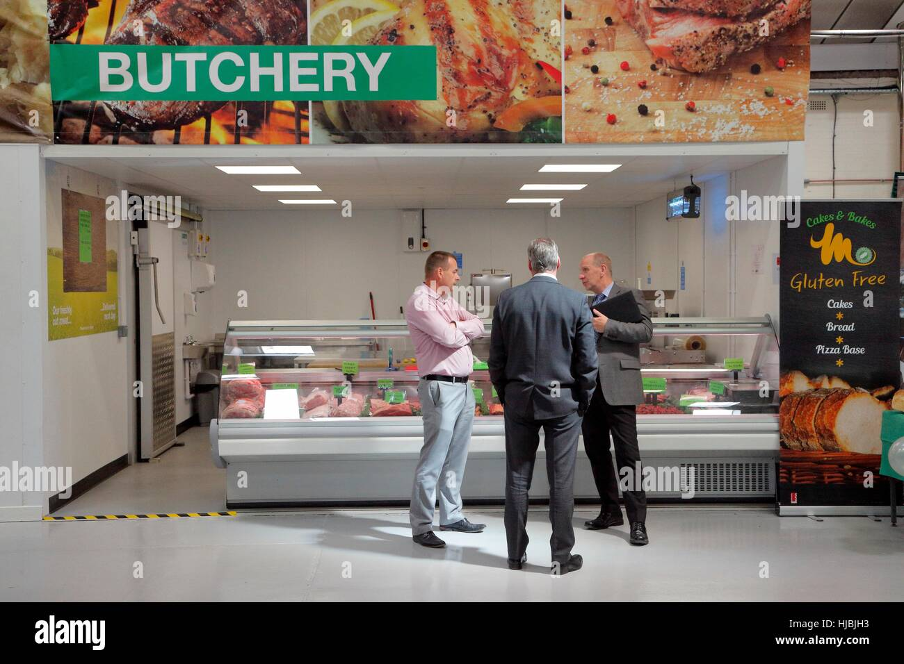 Three men chatting in front of Butchery section of a food wholesaler. - Stock Image