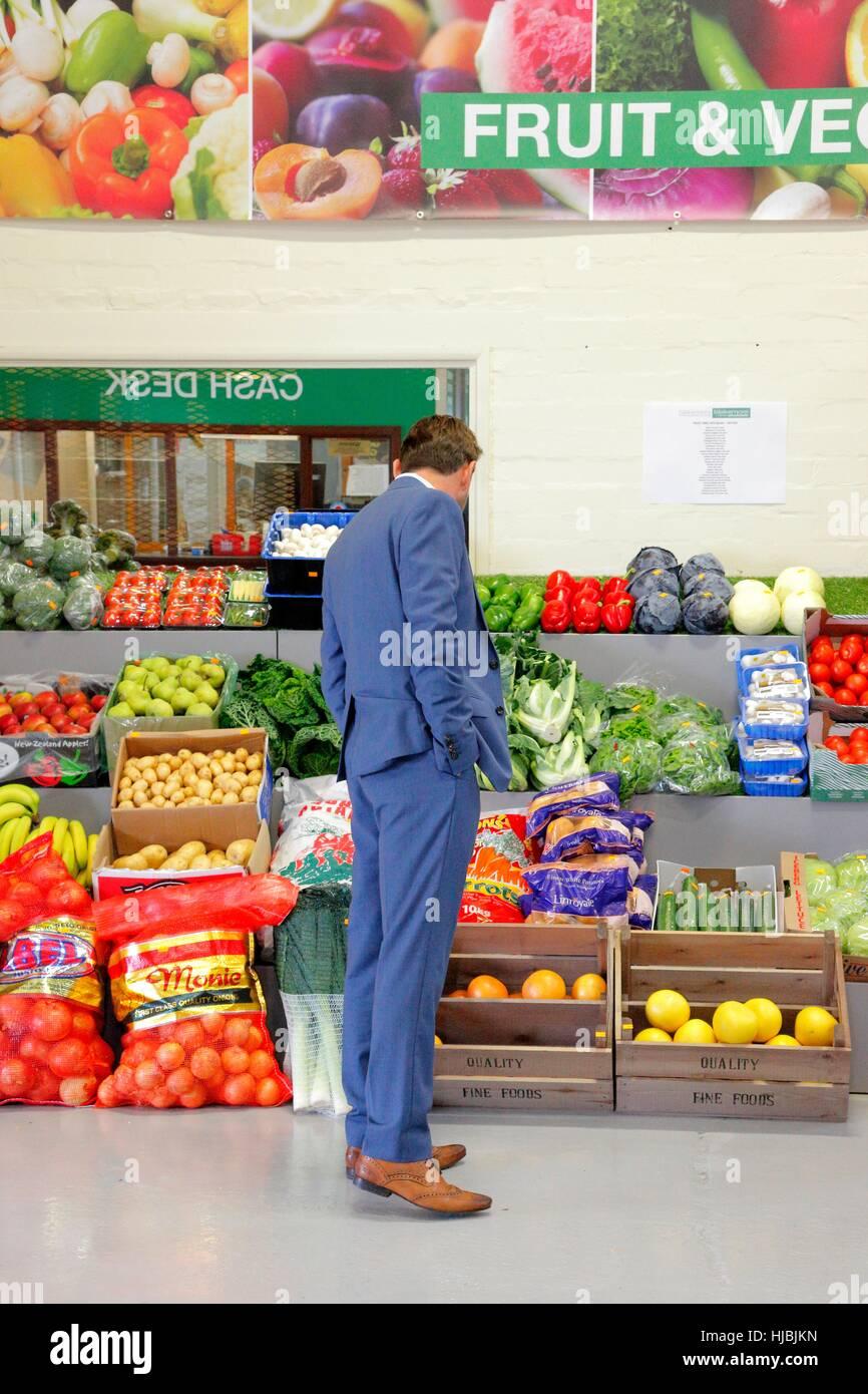 Man in blue suit looking in the fruit and vegetable section of a food wholesaler. - Stock Image