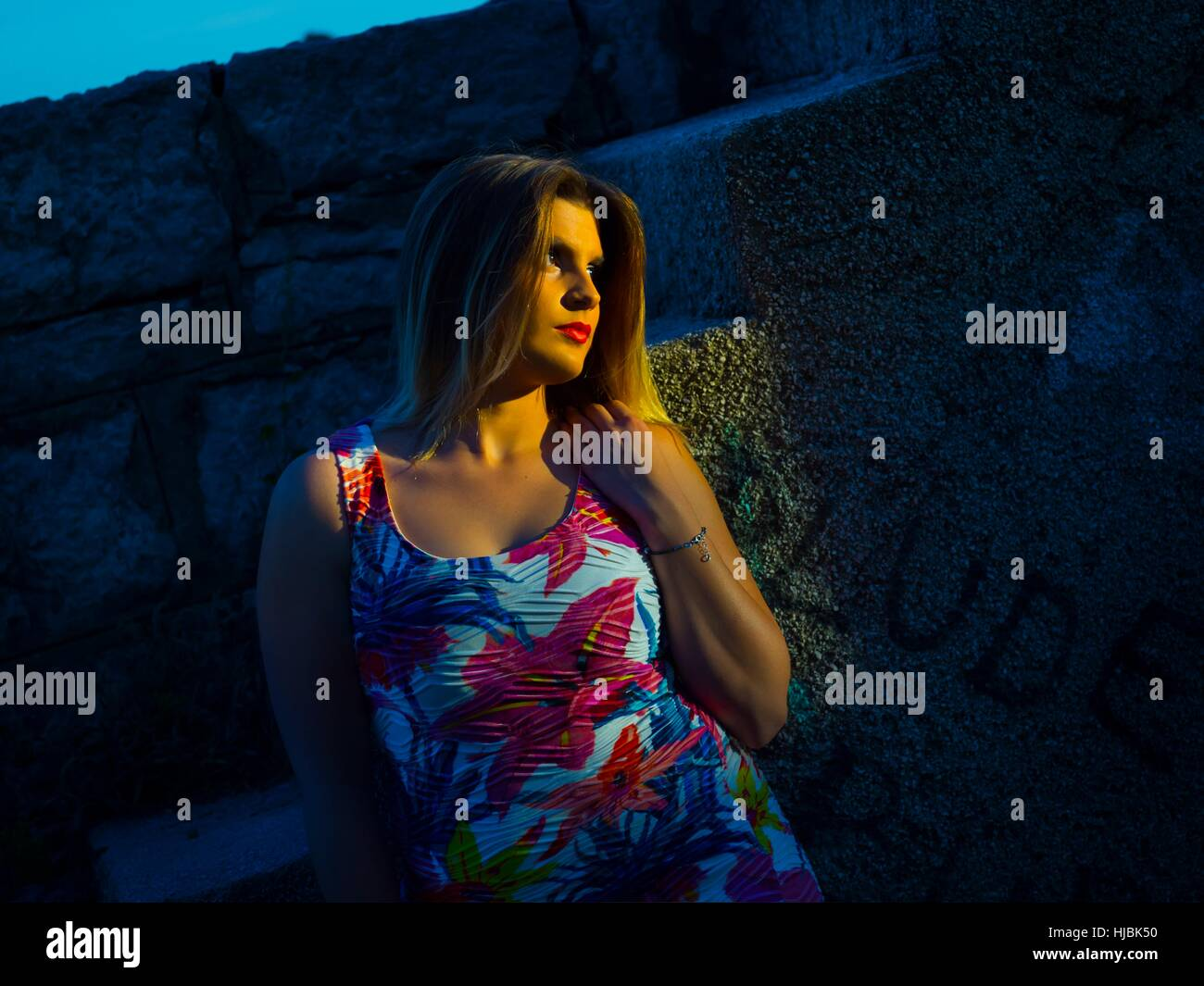 Sunset girl colorful summerdress sundress dress looking away serious Red-lips contrasty dark sun-lighted sidelight - Stock Image
