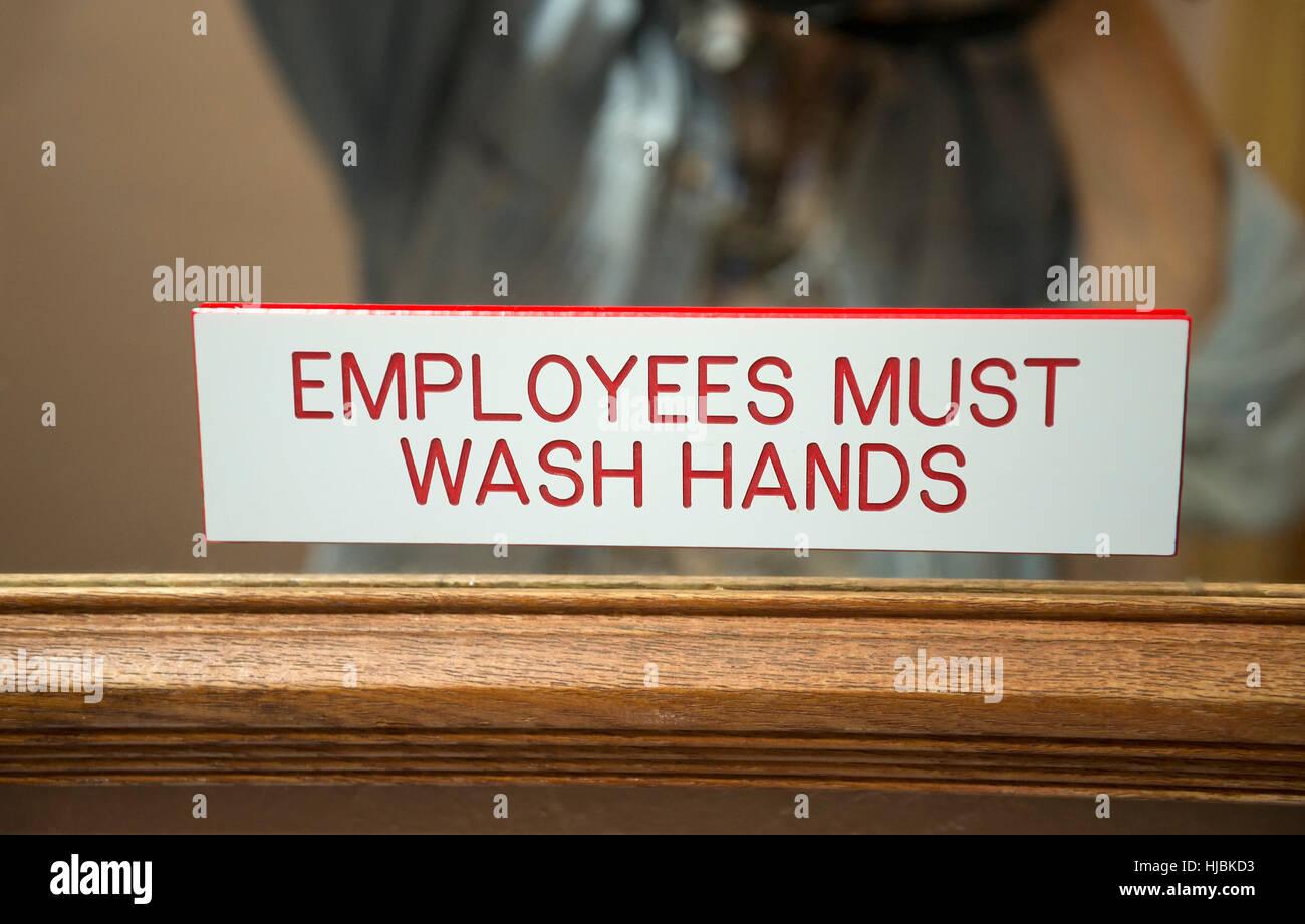 Employees must wash hands sign in restaurant bathroom. - Stock Image