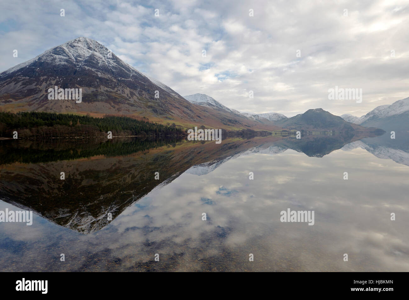 Mountains rocks and trees reflected in the calm surface of Crummock Water, Keswick, Cumbria, Lake District, England - Stock Image