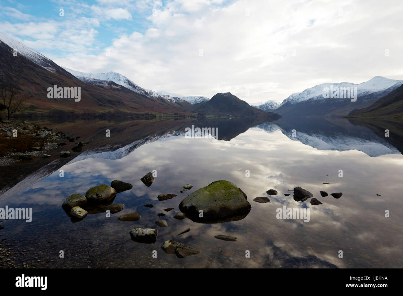 Mountains and rocks reflected in the calm surface of Crummock Water, Keswick, Cumbria, Lake District, England UK. - Stock Image