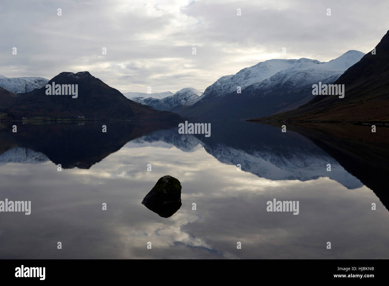 Snow capped mountains and rocks reflected in the calm surface of Crummock Water, Keswick, Cumbria, Lake District, - Stock Image