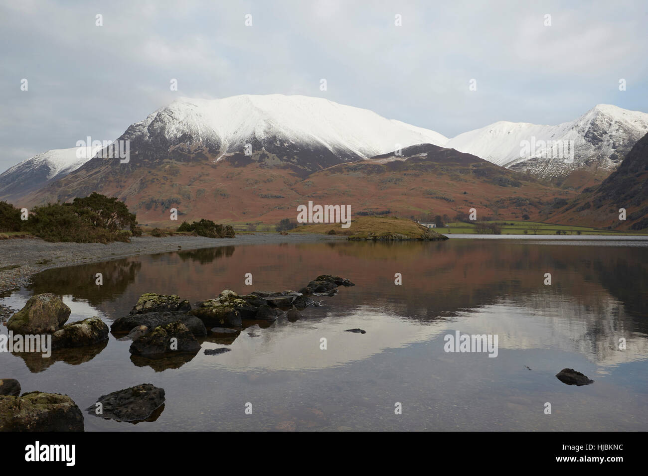 Snow capped mountains, rocks and trees reflected in the calm surface of Crummock Water, Keswick, Cumbria, Lake District, - Stock Image