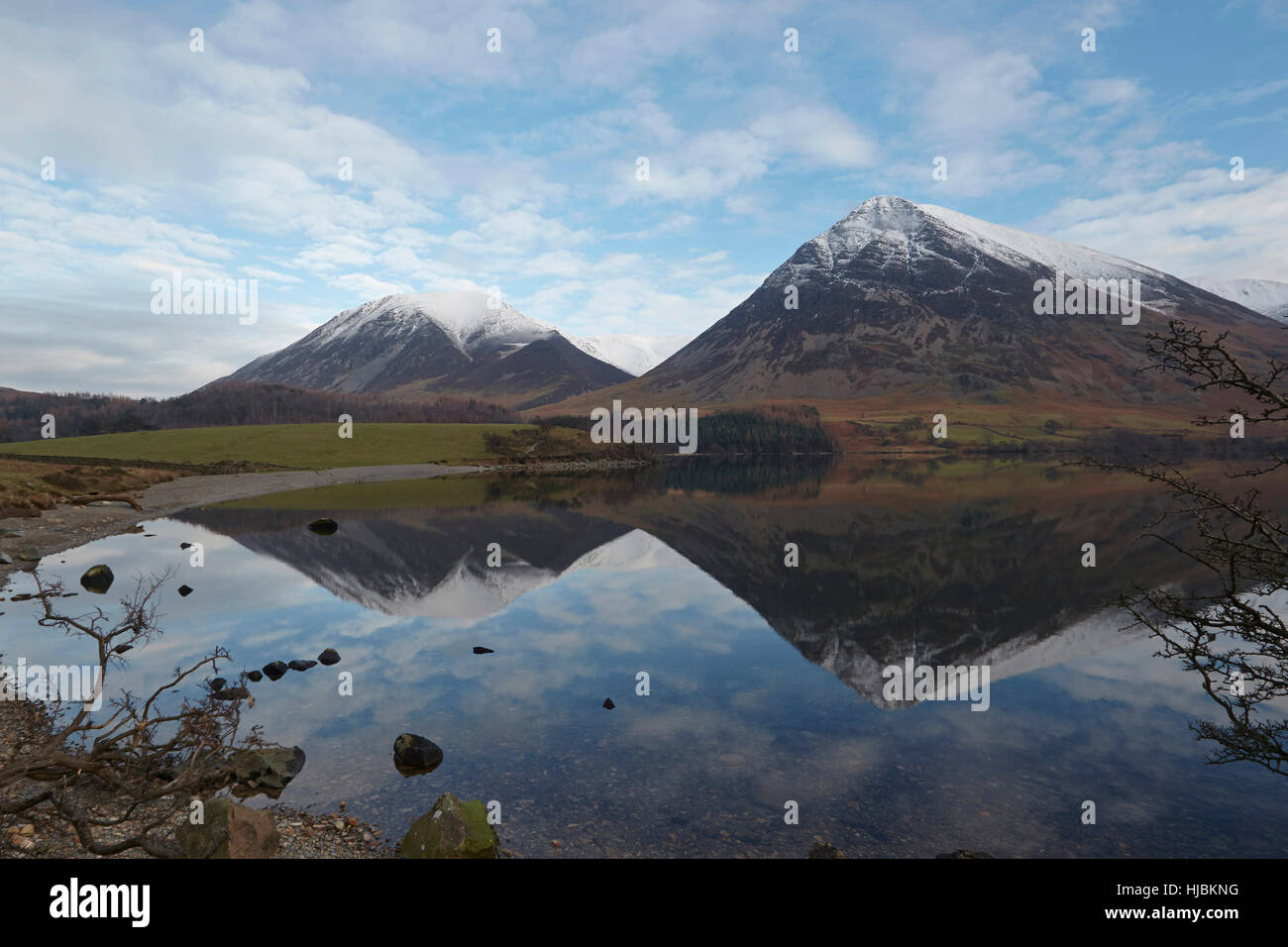 Snow capped mountains, rocks and trees reflected in the calm surface of Crummock Water, Cumbria, Lake District, - Stock Image