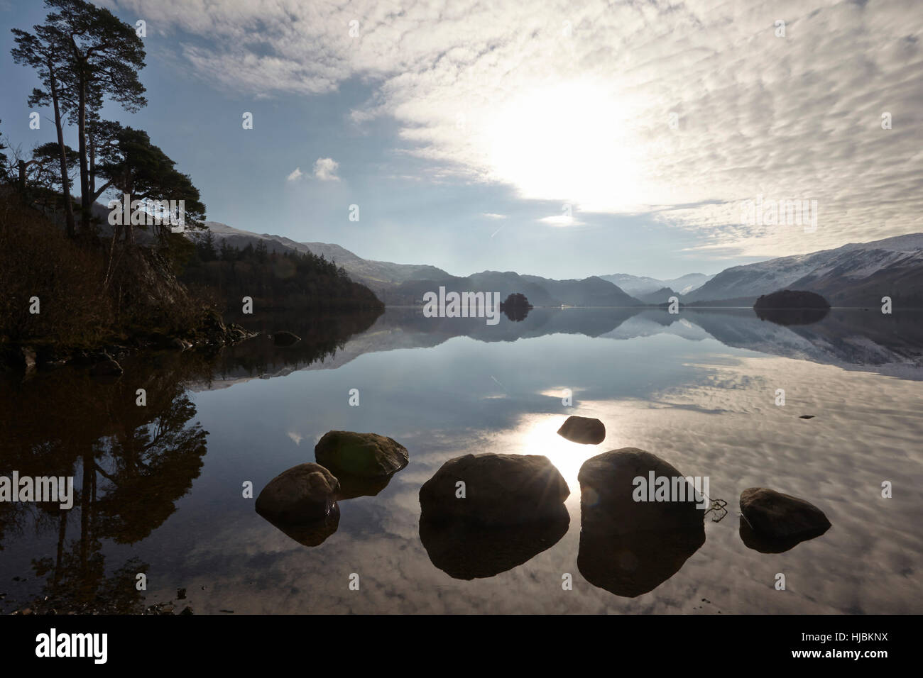 Mountains rocks and trees reflected in the calm surface of Derwent Water, Keswick, Cumbria, Lake District, England - Stock Image