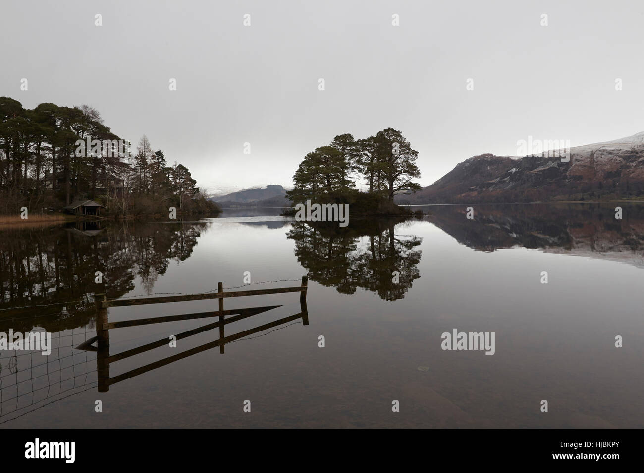 Mountains, a fence and trees reflected in the calm surface of Derwent water, Keswick, Cumbria, Lake District, England Stock Photo