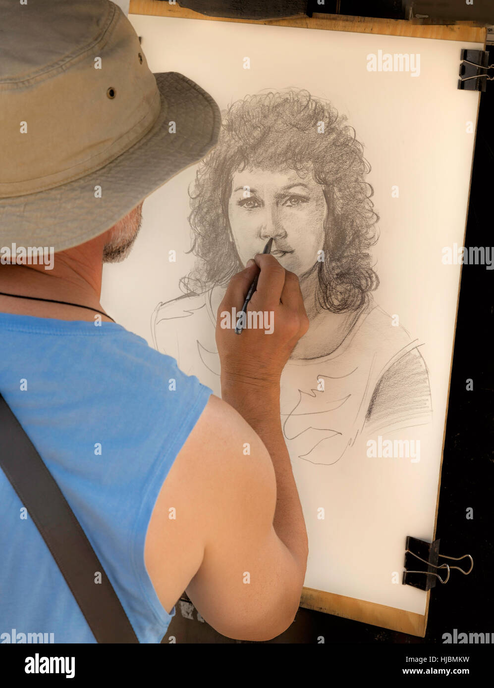 Street artist at work, drawing a portrait of a pretty woman with curly hair, on Charles Bridge, Prague 1, Czech Stock Photo