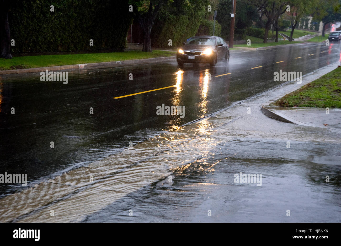 Car driving in rain on wet streets - Stock Image