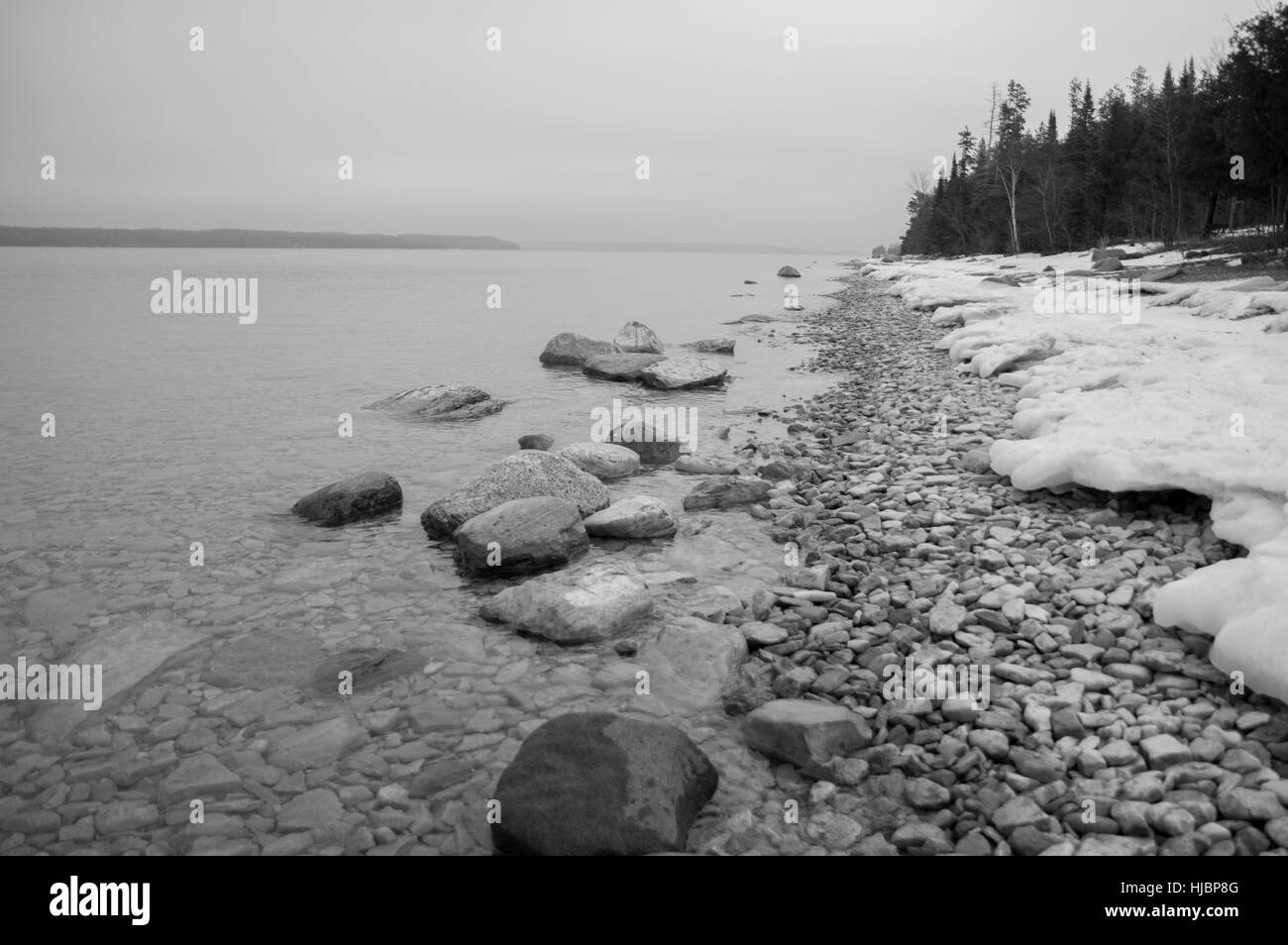 A geometric looking bw image of conifers, snow, rocks and clear lake water and an island on the horizon. - Stock Image