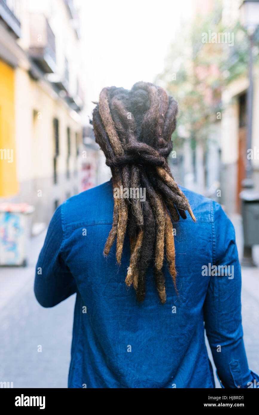 African american man with dreadblocks in the street. Back view. - Stock Image