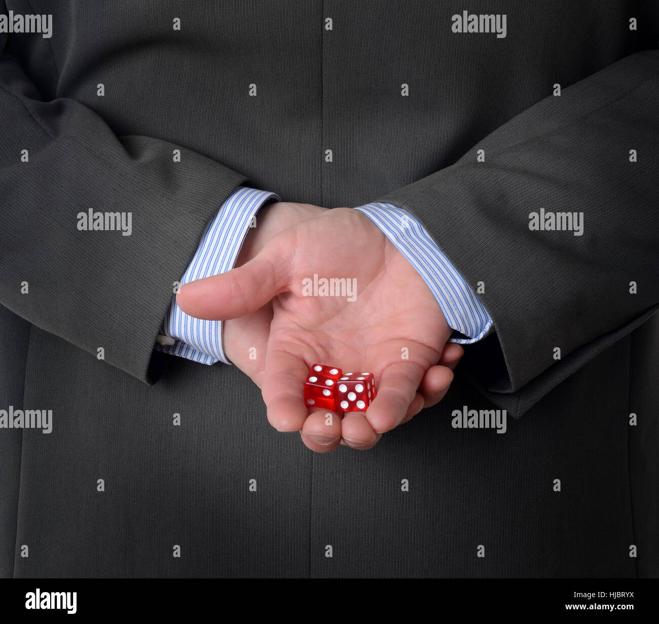 Man in suit with dice behind his back - Stock Image