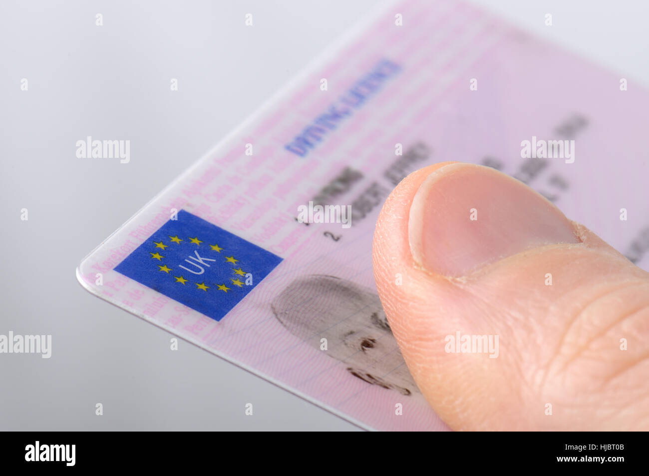 Holding out a driving license Stock Photo