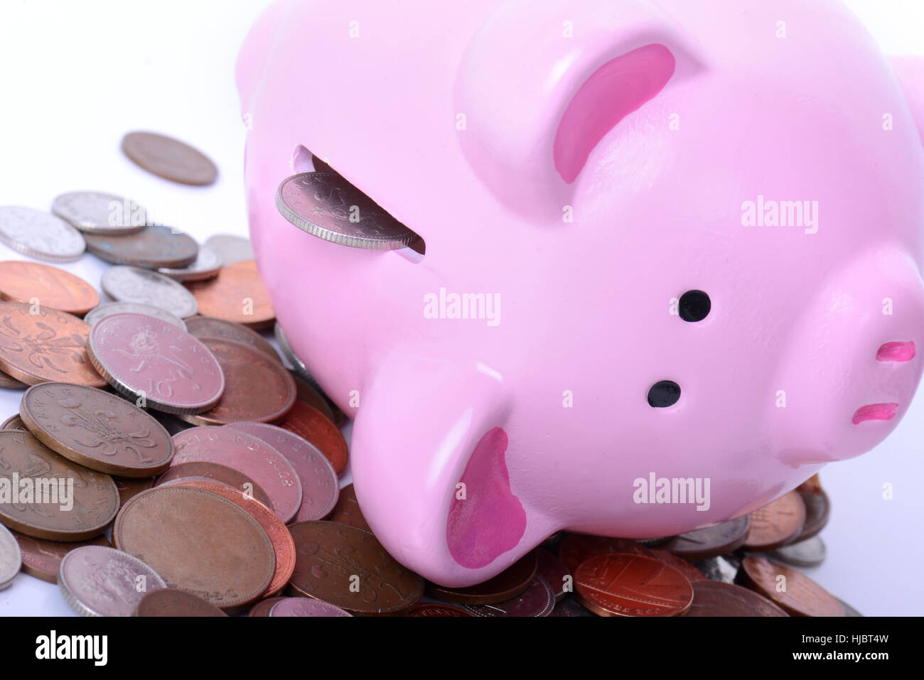 Piggy bank fallen over with coins pouring out concept of debt or finance issues - Stock Image