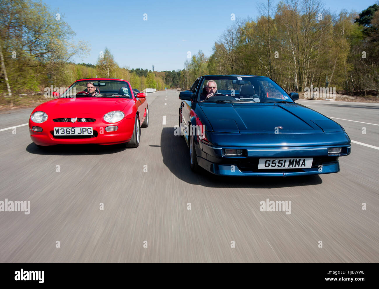 MGF and T-top Mk1 Toyota MR2 mid engine open top sports cars driving together on a summers day - Stock Image