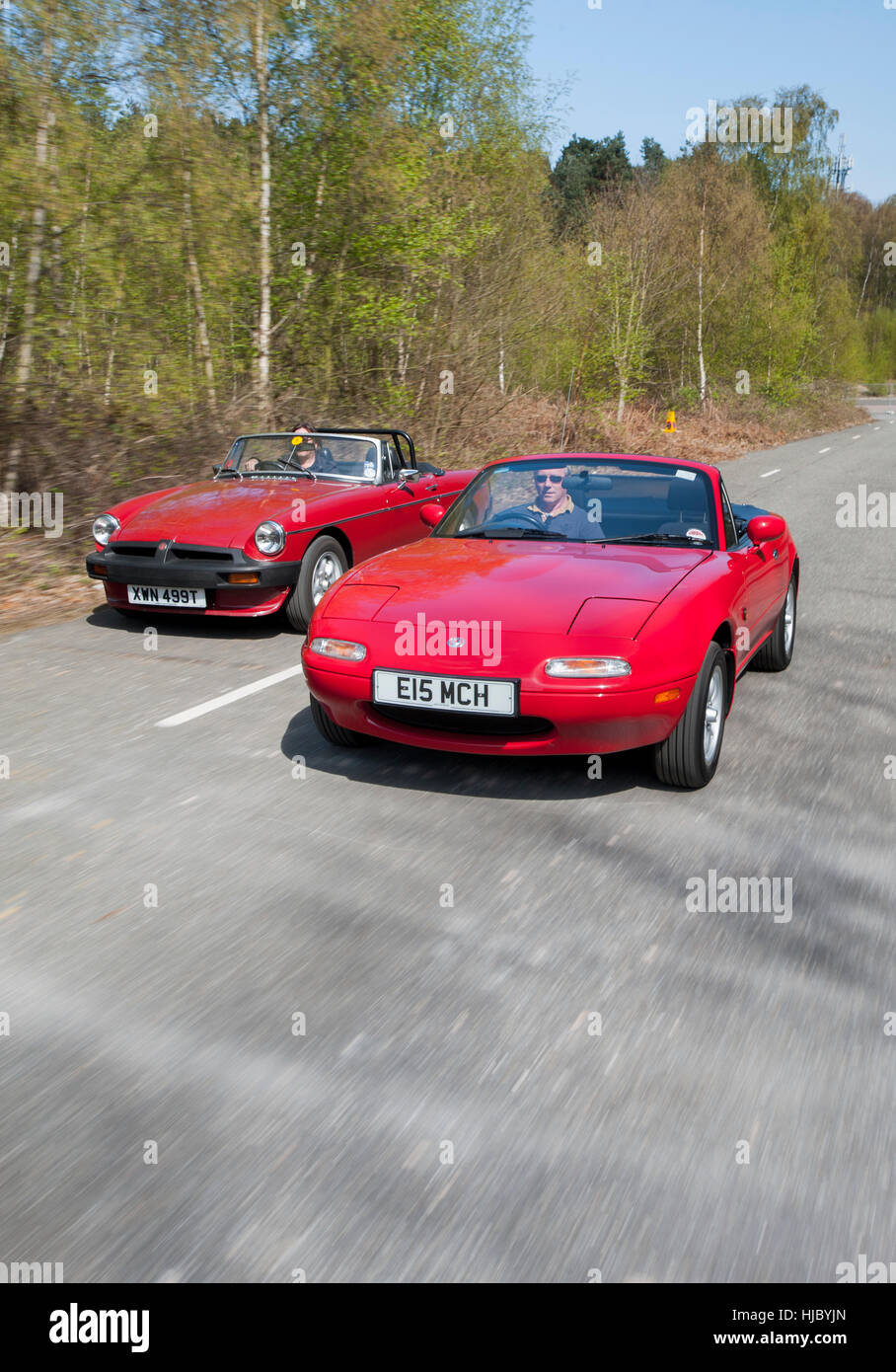 Mazda MX5 and MGB roadster open top sports cars driving together on a summers day - Stock Image