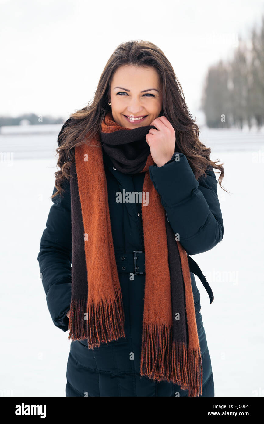 Portrait of smiling young woman in winter park. Winter concept - Stock Image