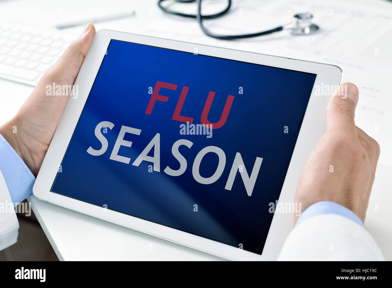 closeup of a young caucasian doctor man holding a tablet computer with the text flu season written in its screen - Stock Image