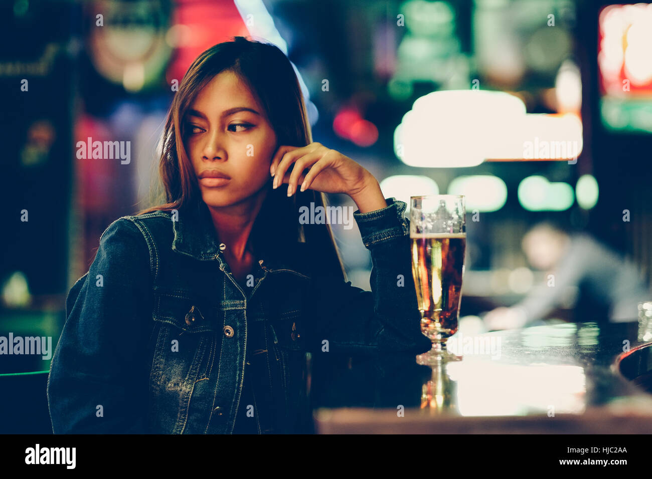 Night life, adult girl waiting in the Bar drinking bear - Stock Image