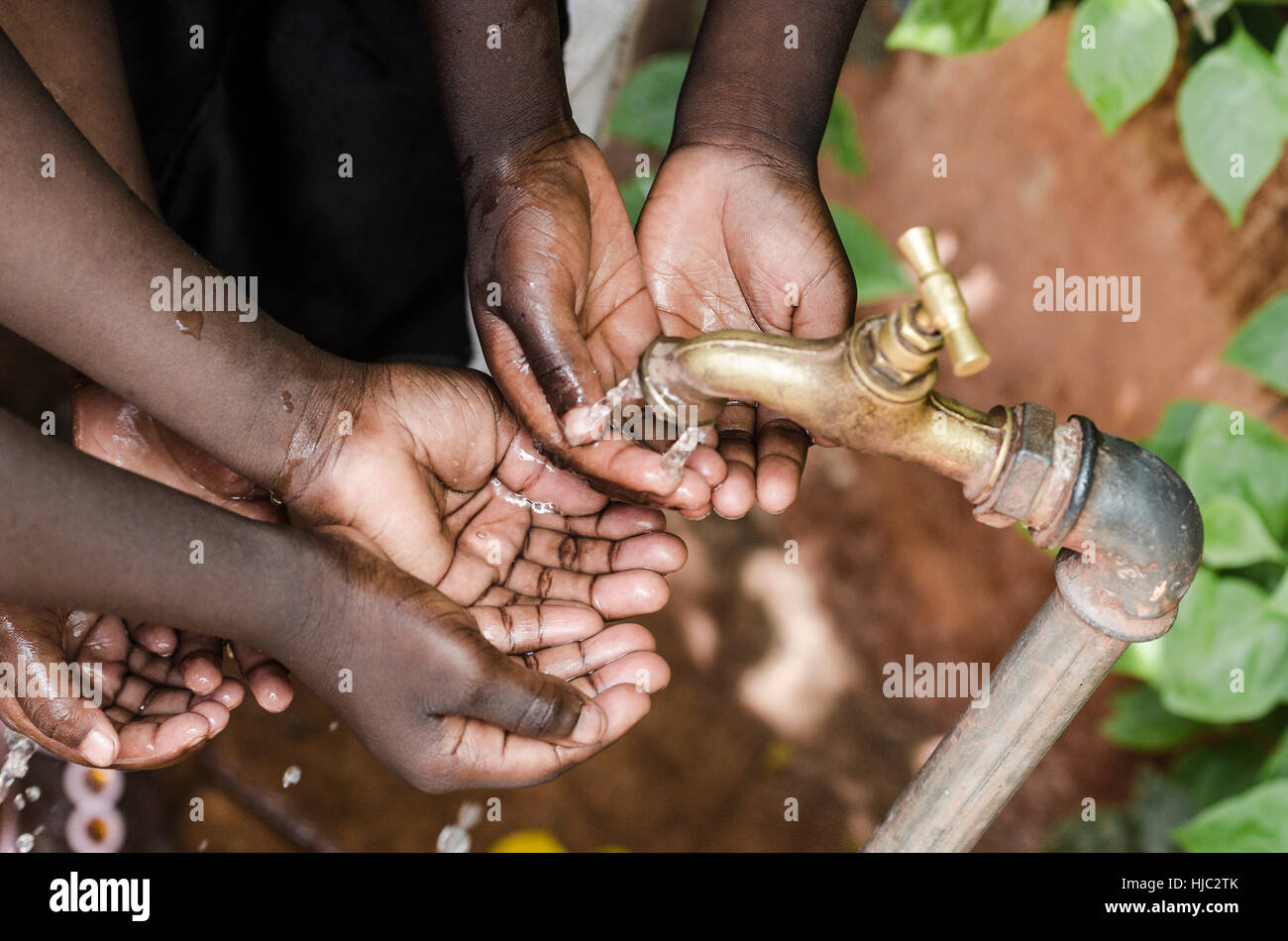 Black Baby Hands Under African Water Tap World Issue - Stock Image