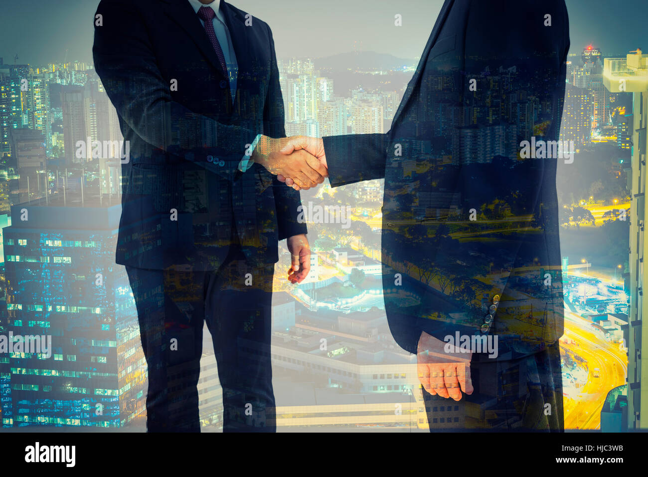 double exposure of commitment from 2 businessman and night cityscape of blue time - can use to display or montage - Stock Image
