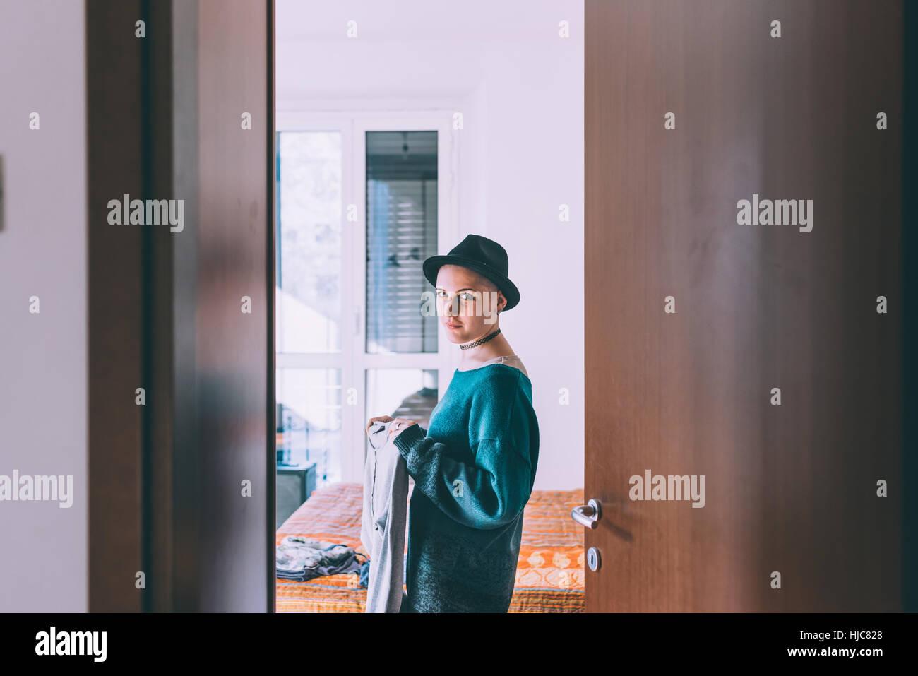 Doorway portrait of young woman wearing trilby standing in bedroom Stock Photo