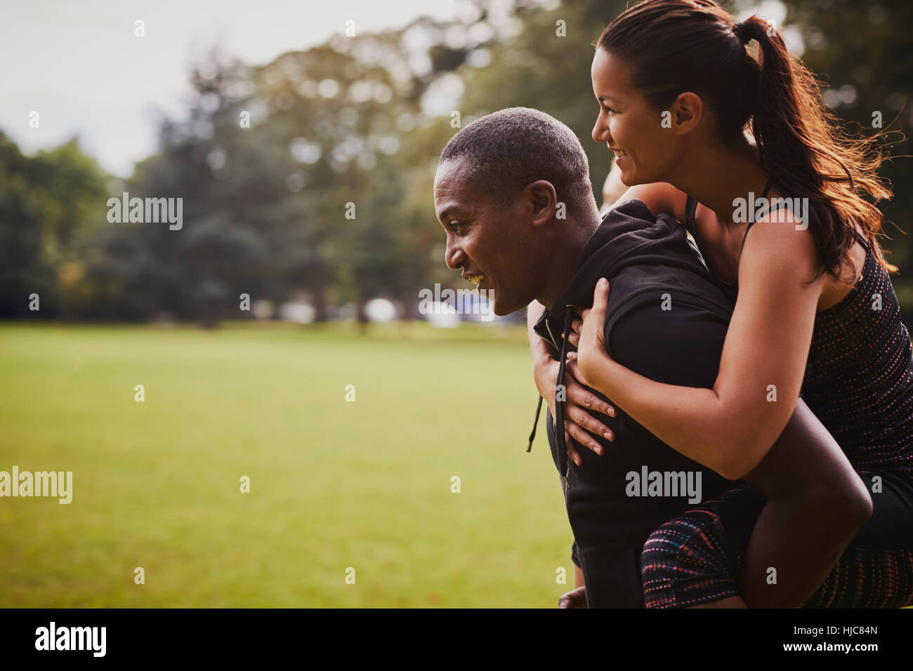 Man and woman having fun training in park, giving piggy back - Stock Image