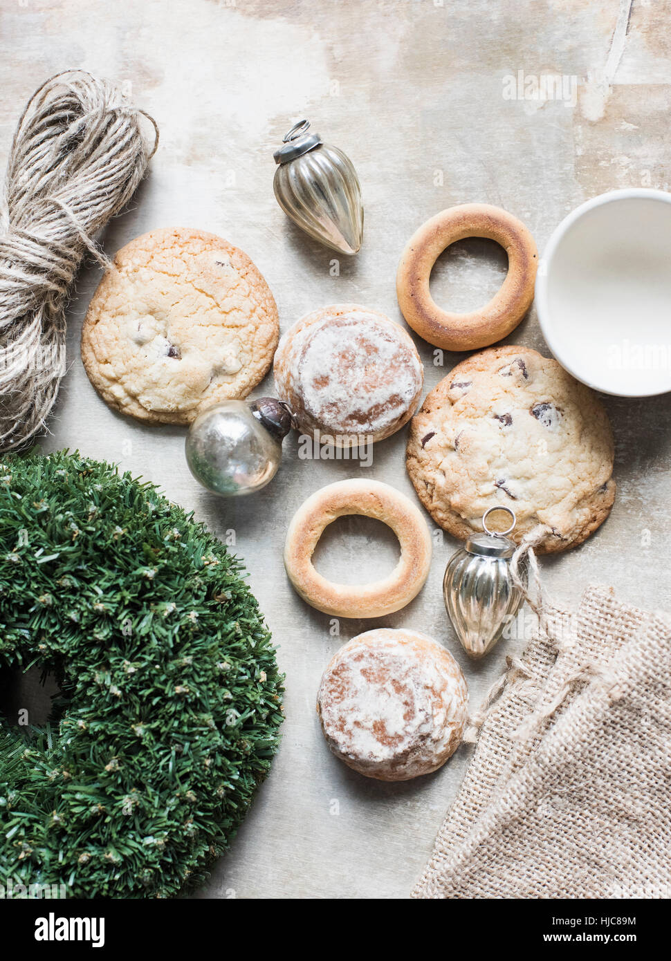 Overhead view of silver Christmas baubles and fresh cookies and bagels - Stock Image