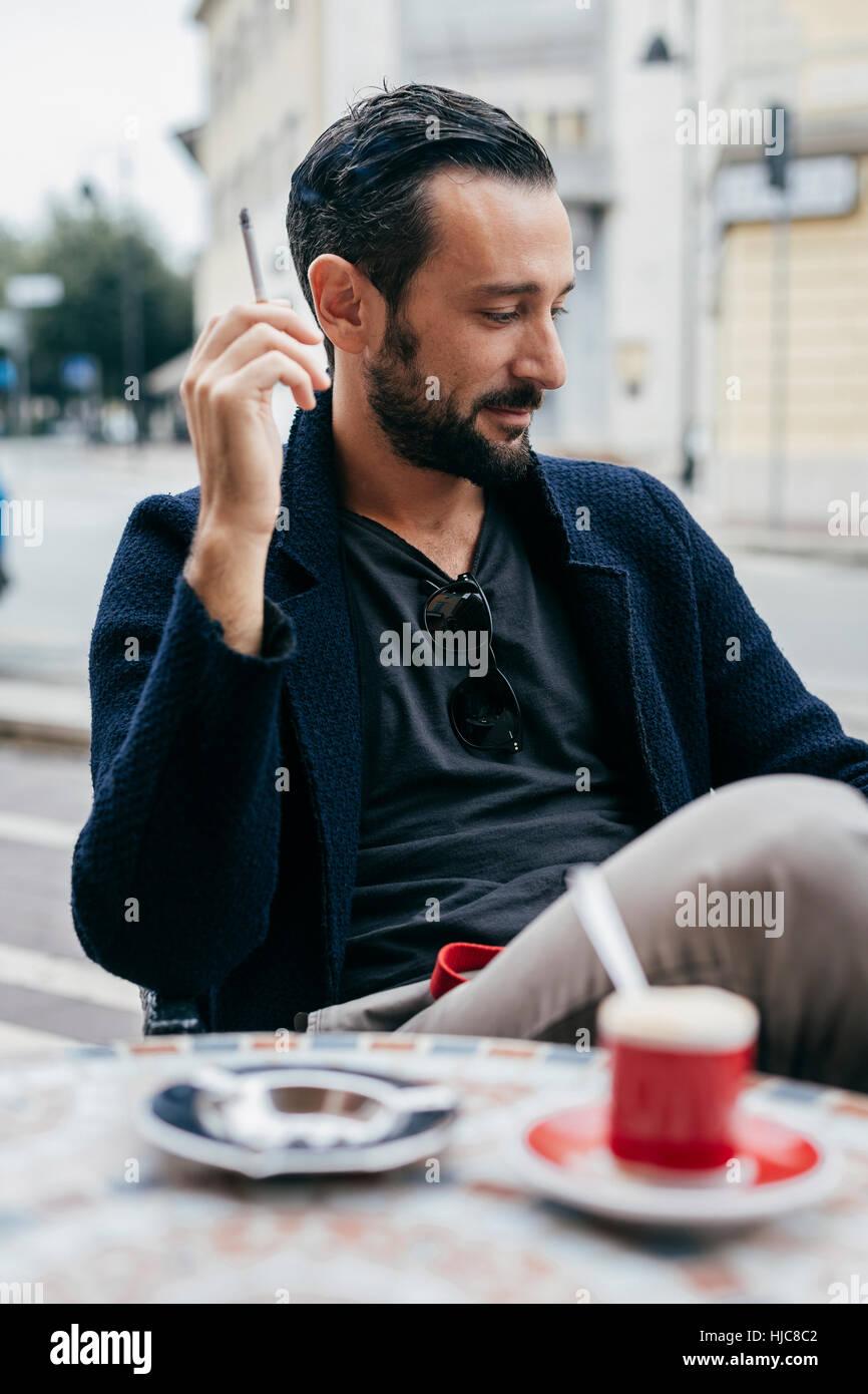Mid adult man smoking cigarette at sidewalk cafe - Stock Image