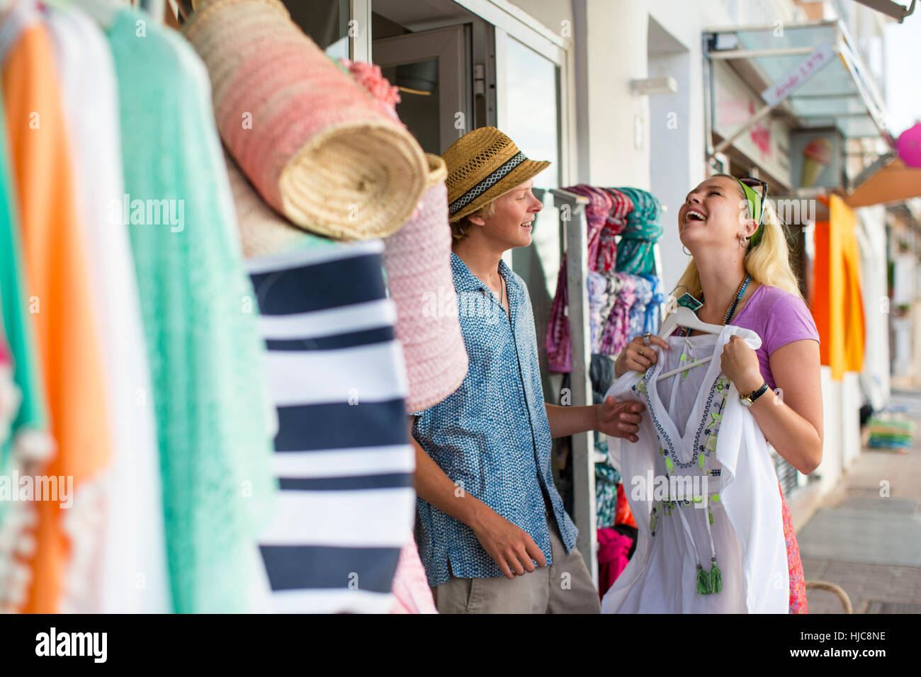 Young couple laughing trying sundress at shop front, Majorca, Spain - Stock Image