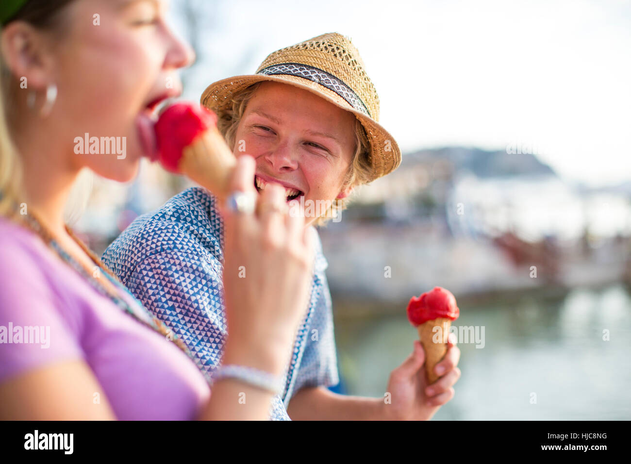 Young couple laughing and eating ice cream cones on waterfront, Majorca, Spain - Stock Image