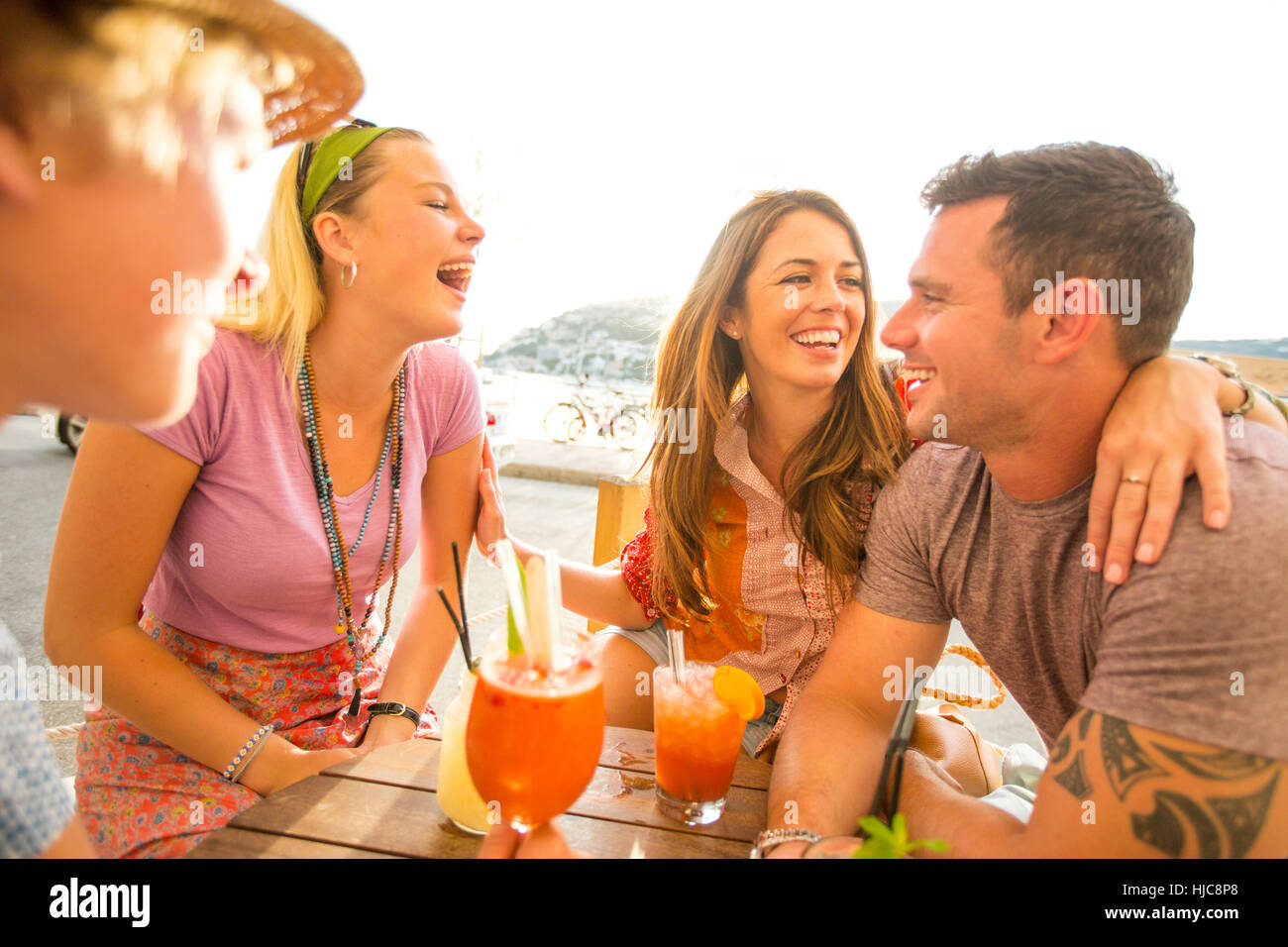 Two adult couples laughing over cocktails at waterfront restaurant, Majorca, Spain - Stock Image