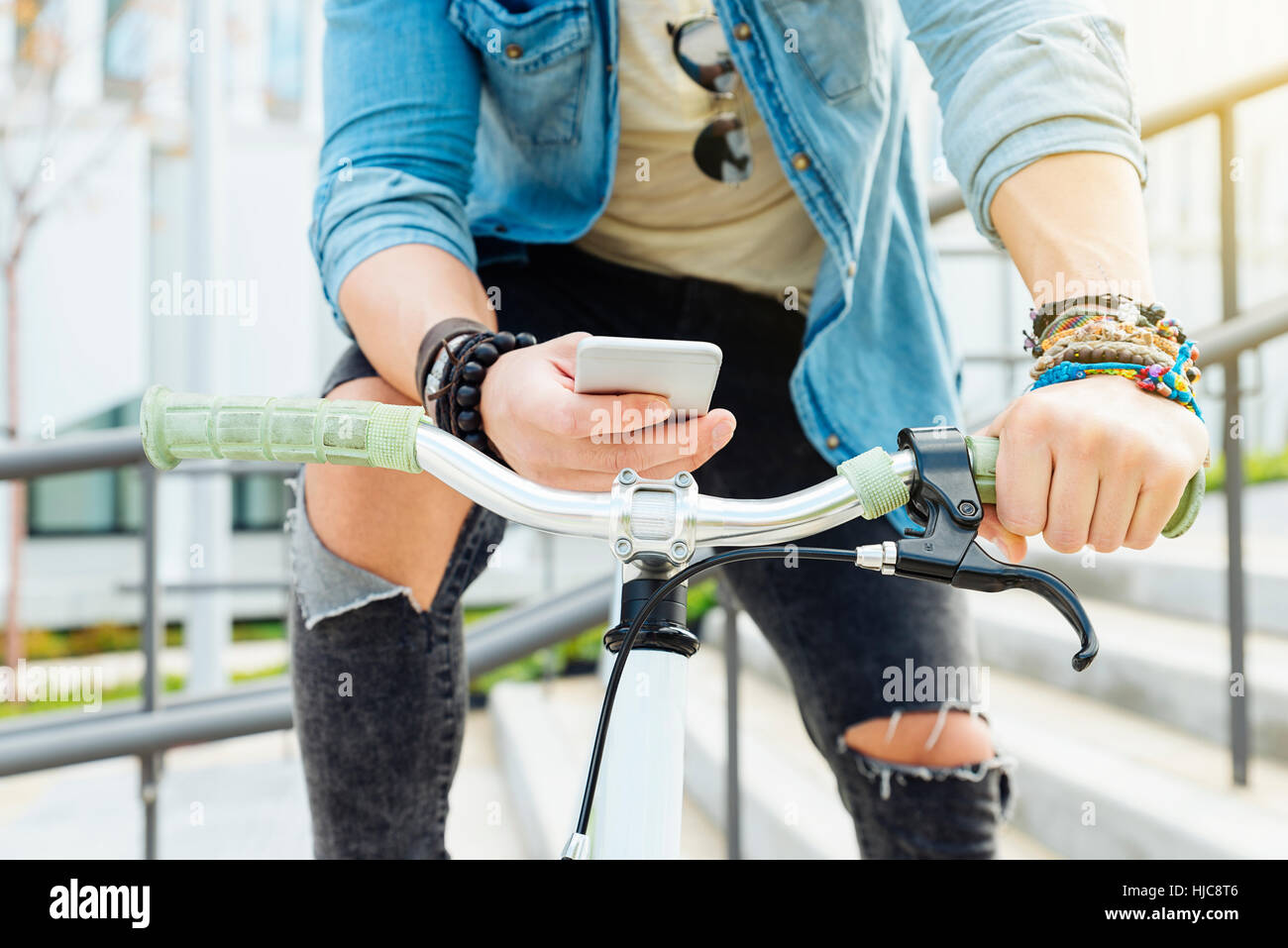 Handsome young man with mobile phone and fixed gear bicycle in the street. - Stock Image