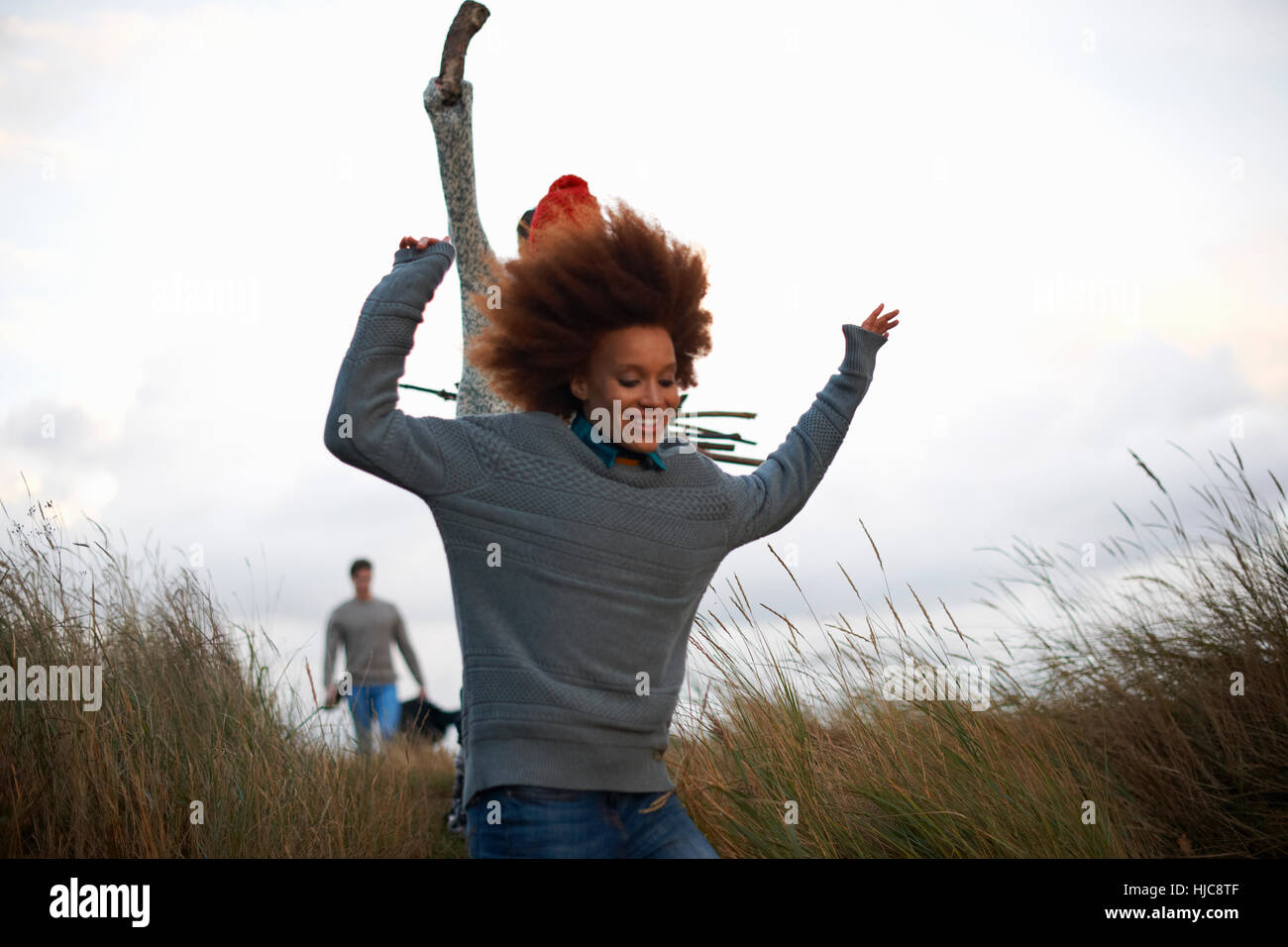 Young adults running in coastal dunes Stock Photo