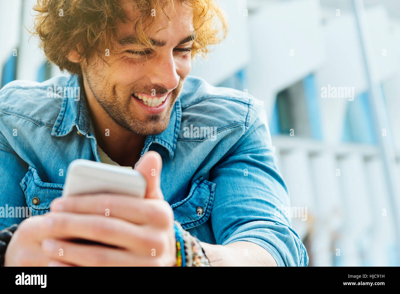 Portrait of Handsome young man smiling when he is using his mobile in the street. - Stock Image