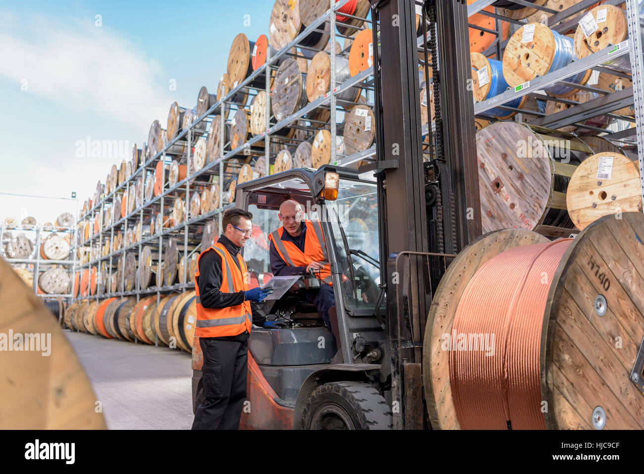 Workers with fork lift truck at cable storage facility - Stock Image