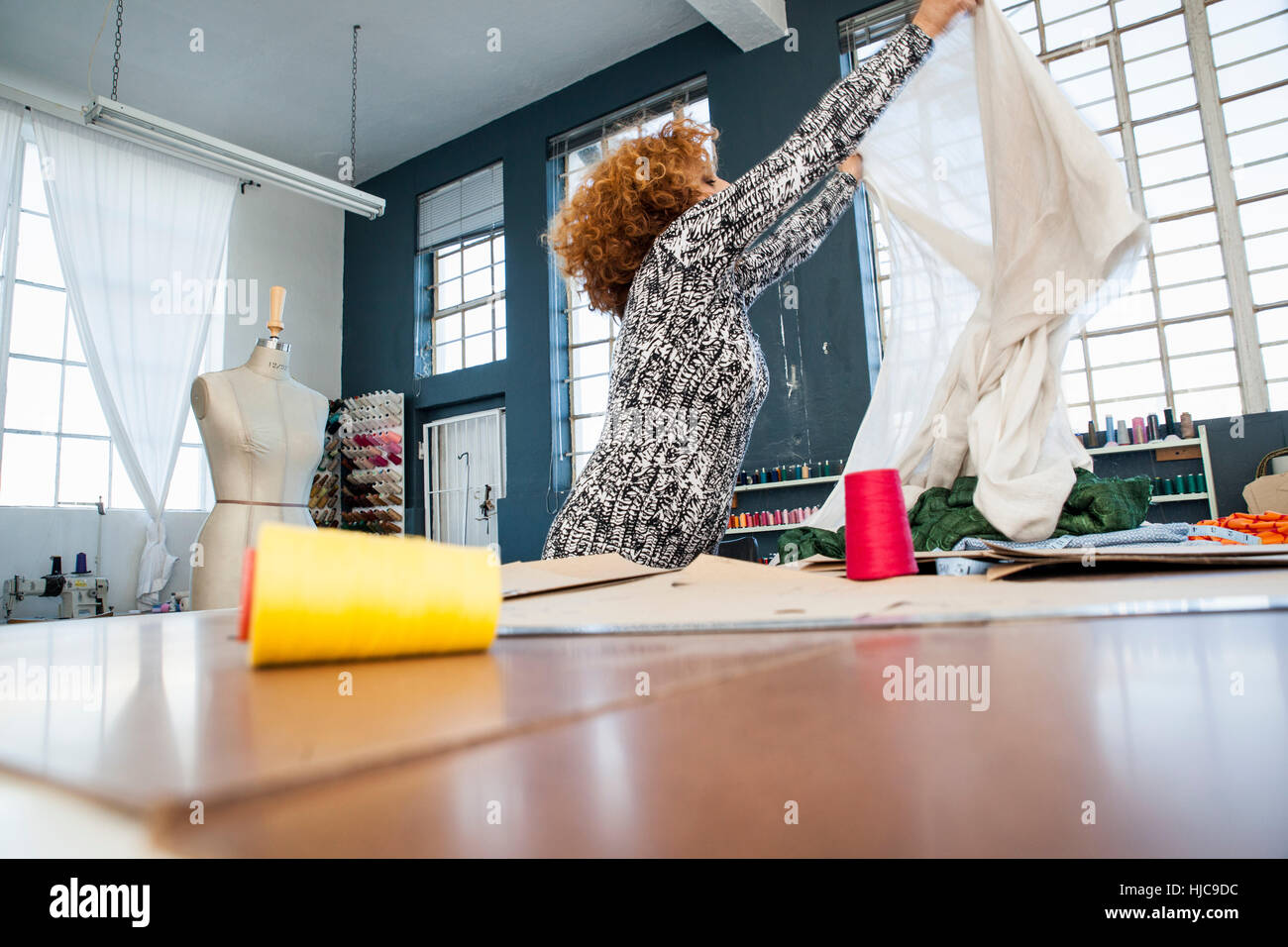 Mature female fashion designer holding up textile by workshop table - Stock Image