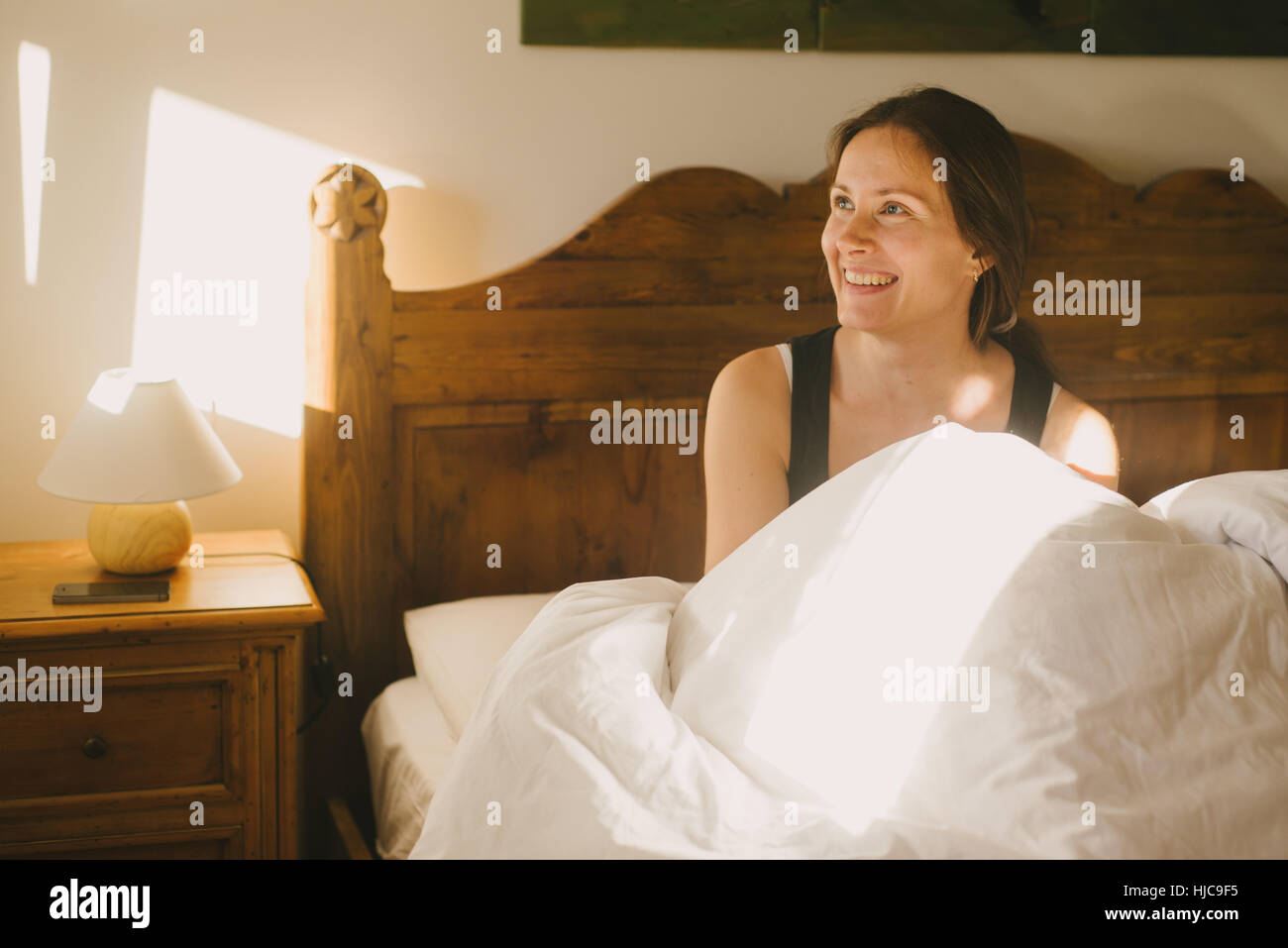 Woman smiling in bed - Stock Image