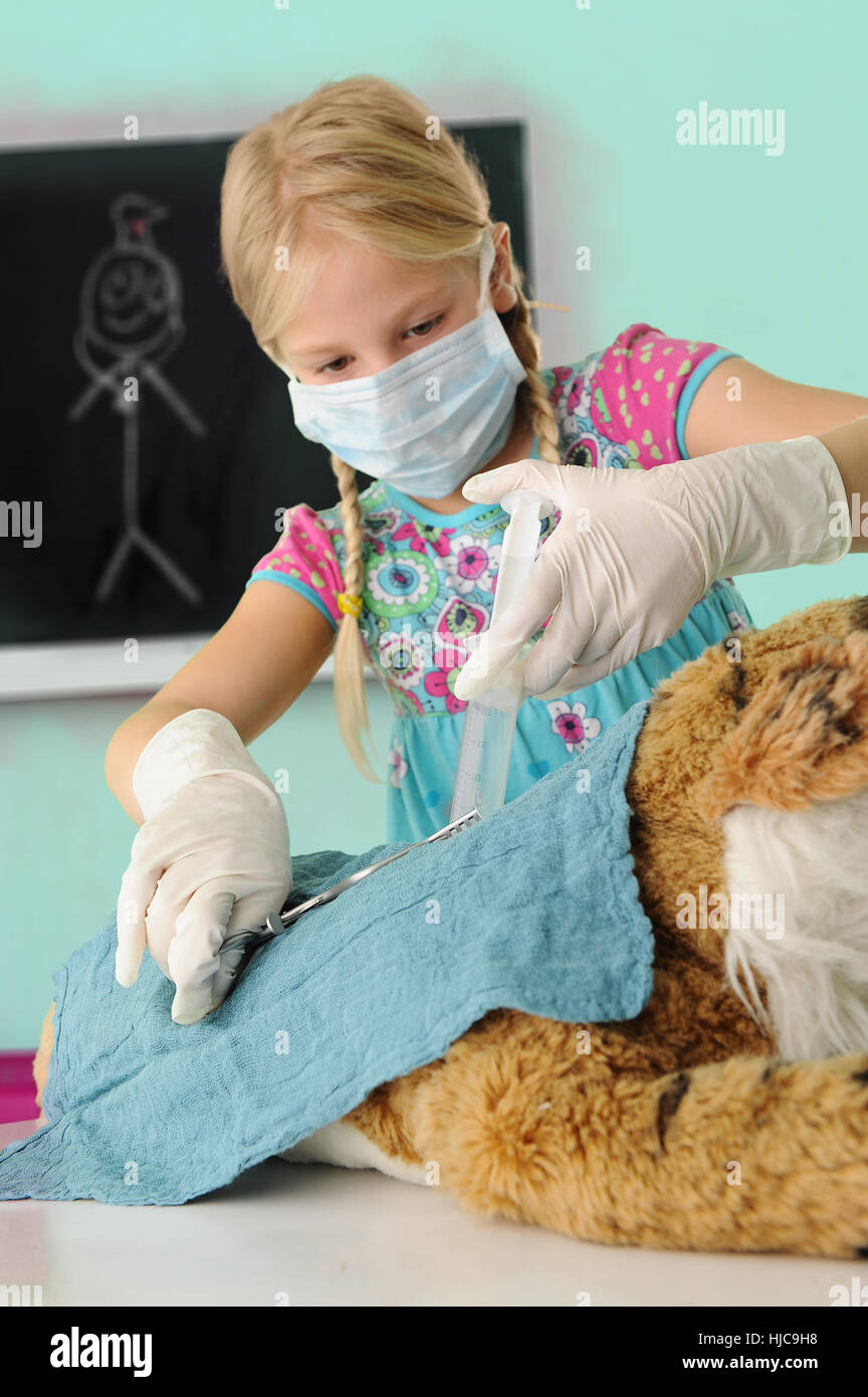 Girl pretending to be vet giving toy tiger syringe injection during operation - Stock Image