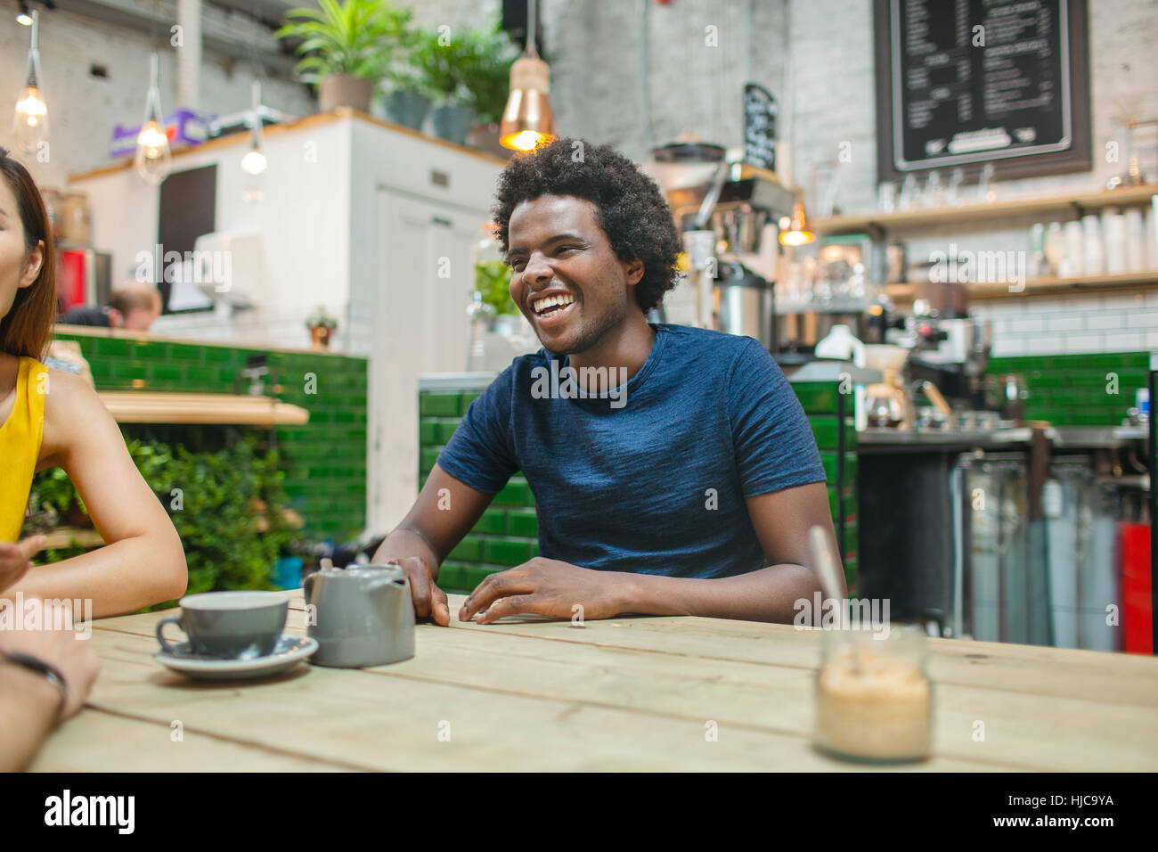 Woman and male friends chatting together in cafe - Stock Image