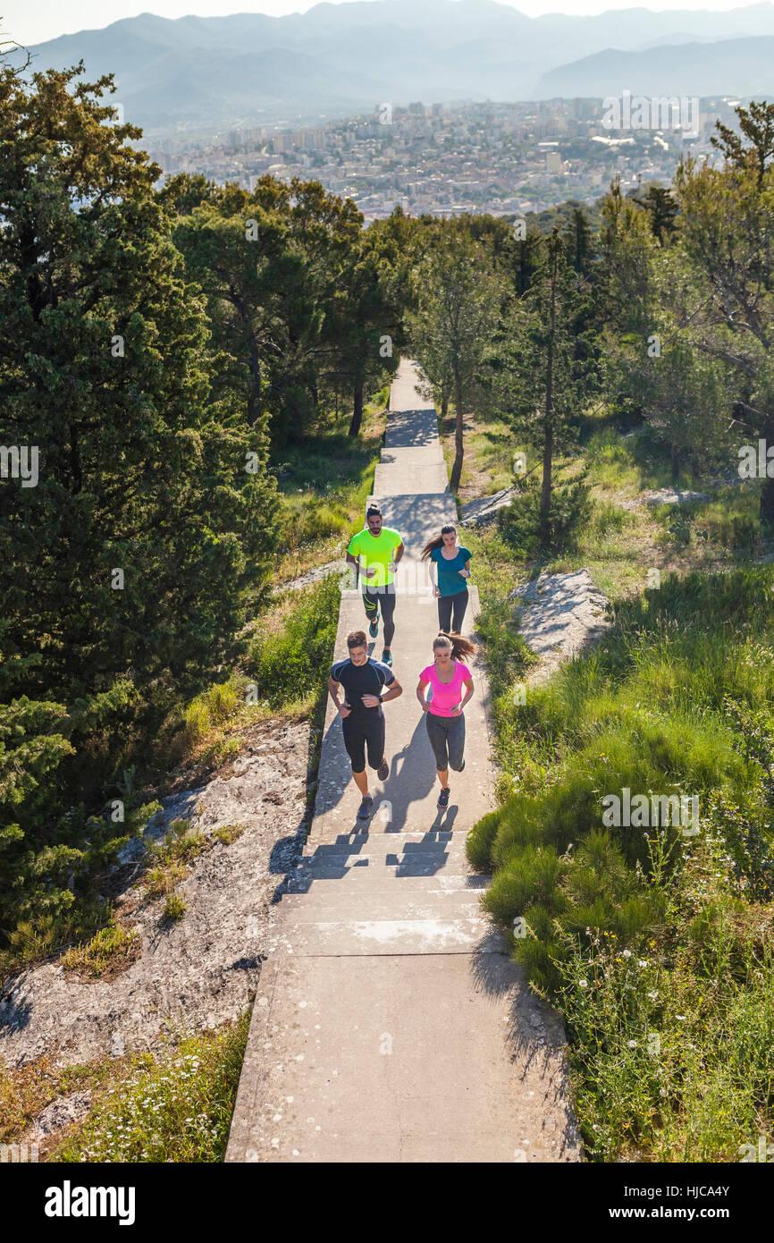Young men and women running in park, Split, Dalmatia, Croatia - Stock Image