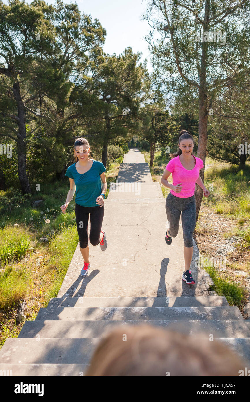 Two female runners running in park, Split, Dalmatia, Croatia - Stock Image