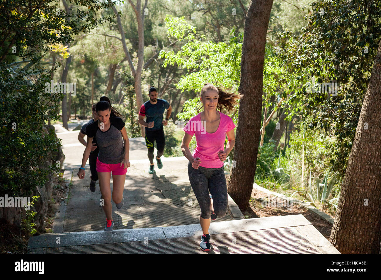 Four male and female runners running in park, Split, Dalmatia, Croatia - Stock Image