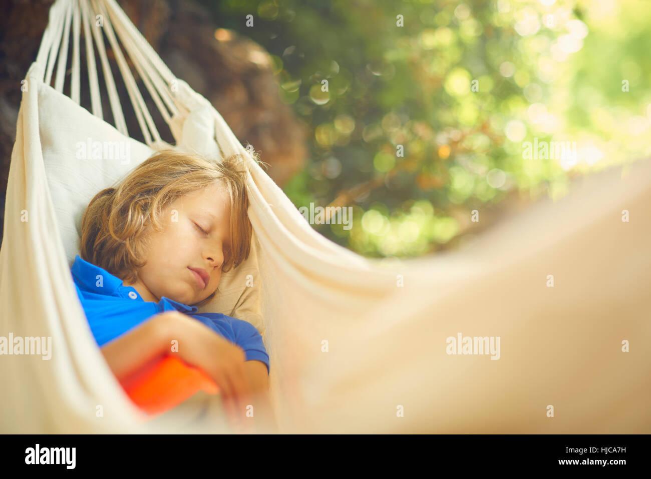 Cute boy reclining in garden hammock asleep - Stock Image