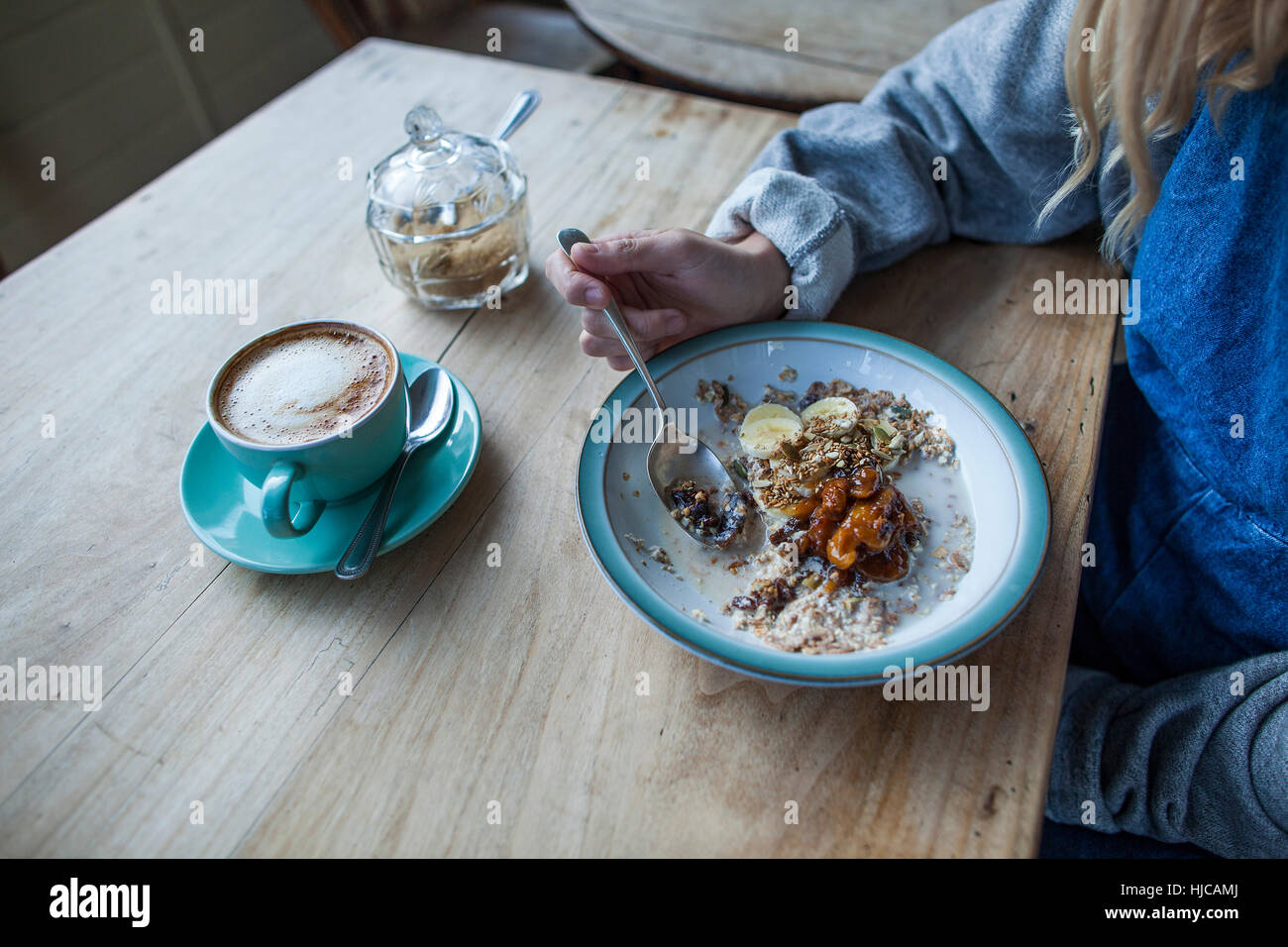 Young woman in cafe, eating muesli, mid section - Stock Image
