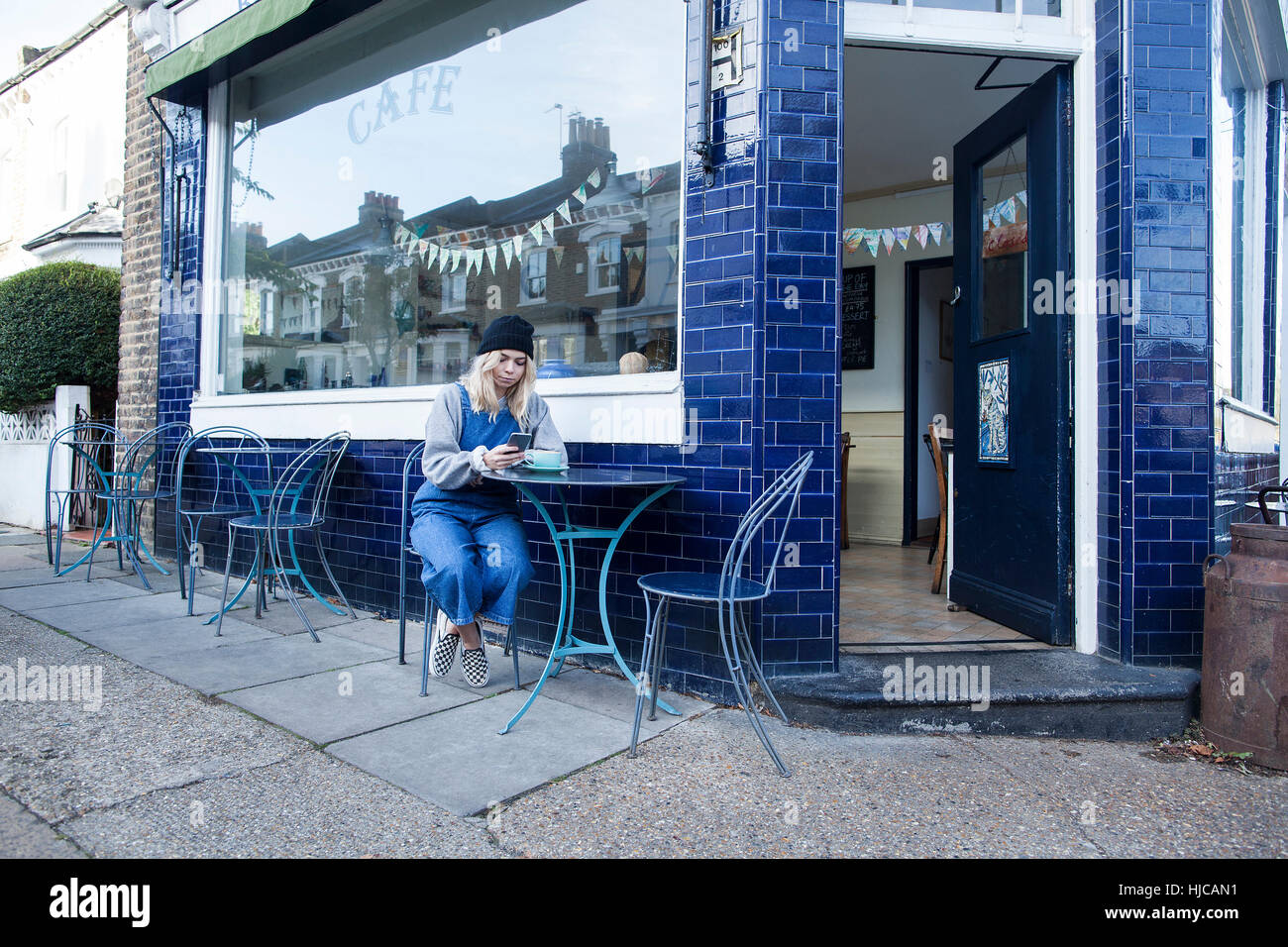 Young woman sitting outside cafe, using smartphone - Stock Image