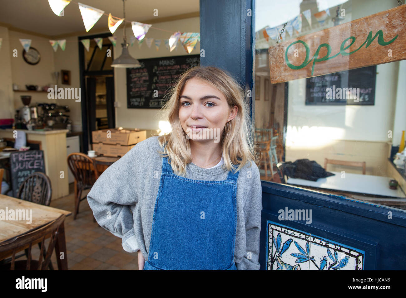 Portrait of young woman standing in doorway of cafe Stock Photo