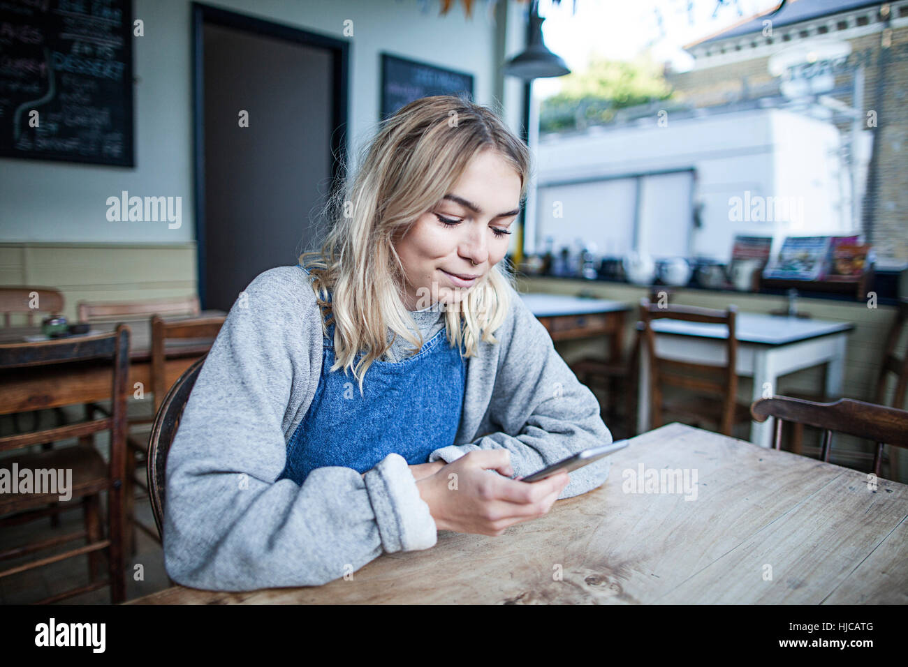 Young woman sitting in cafe, using smartphone, smiling - Stock Image